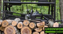 Greenworks Commercial Chainsaw sitting on top a pile of cut up firewood